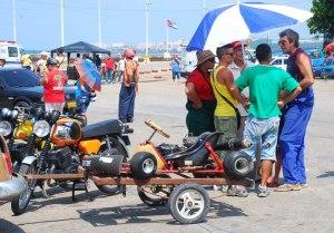 Sobre le trailer un antiguo kart modificado mientras Coqui intercambia opiniones con corredores de kart y motos