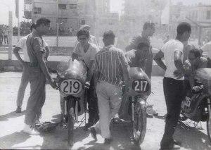 """Mecánicos, pilotos y aficionados en los """"Pits"""" del Malecón previo a una competencia de 250 cc"""