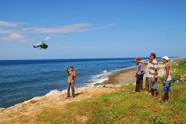 Parte de los miembros del grupo de autogiros. Alexis observa a Vladimir volar el autogiro con forma de helicópero MI-4 de Gilberto