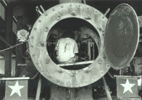 Joven mecanico trabajando en el interior de una locomotora de vapor